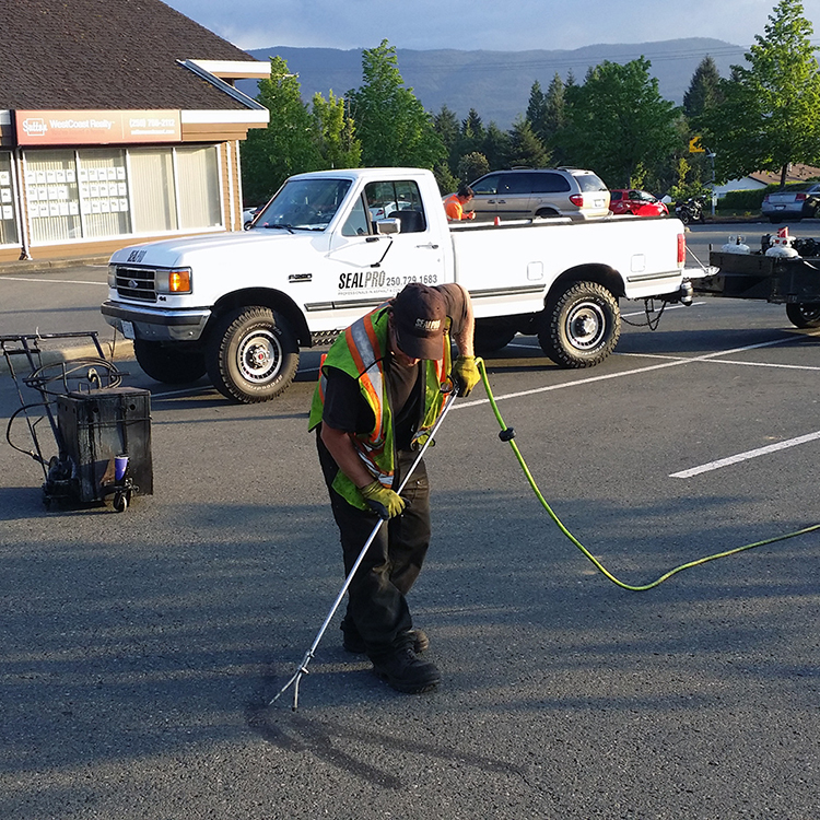 Man sealing cracks in asphalt parking lot